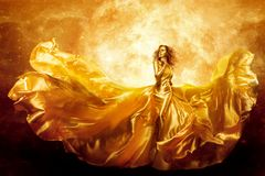 Fashion Model Gold Color Skin, Fantasy Woman Beauty In Artistic Waving Dress, Flying Silk Gown Stock Image