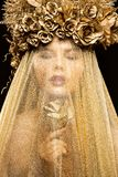 Fashion Model in Gold Flowers Hat Veil, Beautiful Woman Art Portrait with Golden Rose Flower stock image