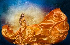 Fashion Model in Golden Dress over Miracle Night Sky Background. Luxury Woman in Long Silk Gown Dance and looking at Stars