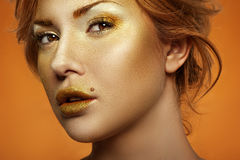 Fashion Model with golden Makeup on Face and Lips Stock Photo