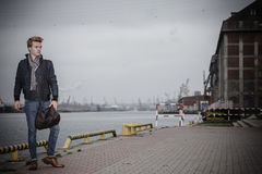 Fashion model guy with bag outdoors Stock Photography