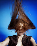 Fashion model with hair blowing in the wind. Blue background royalty free stock image