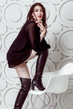 Fashion model with hairstyle and smokey makeup and red lips in black dress and boots posing on white chair. Stock Photography