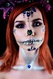 Fashion model with halloween skull makeup with glitter and rhinestones. On black studio background royalty free stock image