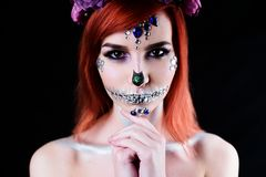 Fashion model with halloween skull makeup with glitter and rhinestones. On black studio background stock photos