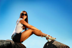 Fashion model in high hill shoes an a stone. Royalty Free Stock Photography