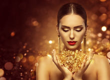 Fashion Model Holding Gold Jewelry in Hands, Woman Golden Beauty. Beautiful Girl Makeup and Luxury Jewellery Stock Photography