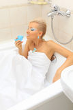 Fashion model kisses dolphin in the bathroom Stock Photography