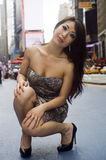 Fashion Model Kneels on Crowded City Street Stock Images