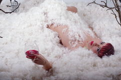 Fashion model lady lying in feathers - Featherdream Stock Images