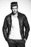 Fashion model in leather jacket with hands in his pockets. Black and white picture of a young fashion model in leather jacket standing with his hands in his Stock Photography