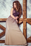 Fashion model with long dress and curly hairstyle and makeup posing near wall with wooden pole. Studio shot Royalty Free Stock Images