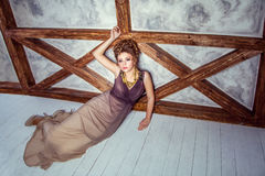 Fashion model with long dress and curly hairstyle and makeup posing near wall with wooden pole. Studio shot Stock Photos