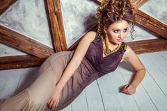 Fashion model with long dress and curly hairstyle and makeup posing near wall with wooden pole. Studio shot Royalty Free Stock Photography