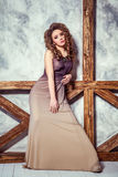 Fashion model with long dress and curly hairstyle and makeup posing near wall with wooden pole. Studio shot Stock Images