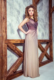 Fashion model with long dress and curly hairstyle and makeup posing near wall with wooden pole. Studio shot Stock Photography