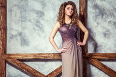 Fashion model with long dress and curly hairstyle and makeup posing near wall with wooden pole. Studio shot Stock Photo