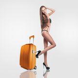 Fashion model with long hair in black lingerie going on a trip with an orange suitcase Stock Image
