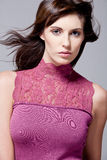 Fashion model with long hair wearing pink dress. Royalty Free Stock Image