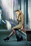 Fashion model with long sexy legs sitting on bench thinking Royalty Free Stock Images