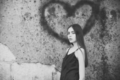 Fashion model. Love symbol of spray paint and girl. Valentines day holiday celebration concept. Woman posing with heart graffiti on grey wall. Model wearing royalty free stock images