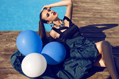 Fashion model in luxury dress posing with balloons Stock Photos