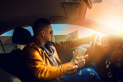 Fashion model male driving car with lot of money in hand Royalty Free Stock Image
