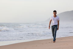 Fashion model man walking on the sand beach Stock Images