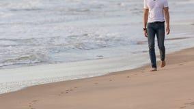 Fashion model man walking on the sand beach Stock Photography