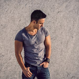 Fashion model man wearing grey t-shirt and jeans posing in front of the wall. Portrait of fashion model man wearing grey t-shirt and jeans posing in front of the Royalty Free Stock Images