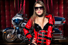 Fashion model with motorbike. Fashion model wears red clothes with motorbike Stock Photography