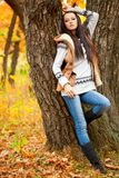 Fashion model near tree in autmn park Stock Photo
