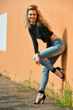 Fashion model with perfect slim body wearing cropped top and ripped jeans posing sexy outside Royalty Free Stock Photography