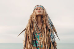 Fashion model portrait outdoors. boho style young woman with headdress made of feathers. Boho style fashion model outdoors portrait stock photo