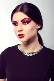 Fashion model portrait. Scarlet makeup. Black arrows. Royalty Free Stock Image