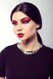 Fashion model portrait. Scarlet makeup. Black arrows. Royalty Free Stock Image