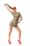Fashion Model Poses. Young beautiful woman in gold mini dress, red high heels and sun visor, posing and holding in hand her ponytail. Full length studio shot Royalty Free Stock Photography