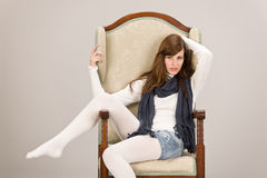 Fashion model posing on antique armchair Stock Photo