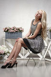 Fashion model posing in the chair Royalty Free Stock Image