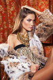 Fashion model posing in a fur coat in luxury interior. Always mo Royalty Free Stock Image