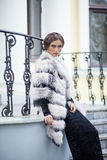 Fashion model posing in a fur coat on a stairs Royalty Free Stock Image