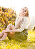 Fashion model posing on grass in park Royalty Free Stock Image