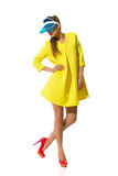 Fashion Model Posing In Plastic Sun Visor Cap. Fashionable young woman posing in red high heels, yellow mini dress and blue plastic sun visor. Full length studio Stock Photo