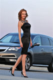 Fashion model posing pretty in front of sport SUV Royalty Free Stock Images