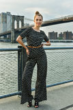 Fashion model posing pretty in jumpsuit and  hair bun style on the pier. Royalty Free Stock Images