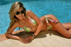 Fashion model posing pretty by swimming pool wearing designers bikini stock photos