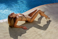 Fashion model posing pretty by swimming pool Stock Photography