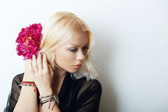 Fashion model posing. With red flower. Portrait of a beautiful blond woman with blue eyes Stock Photos