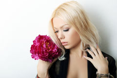 Fashion model posing. With red flower. Portrait of a beautiful blond woman with blue eyes Royalty Free Stock Image