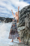 Fashion model posing at sea. Young fashion woman in a long dress posing near sea water Stock Photography